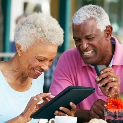 an old man looking besides an old woman smiling while holding a tablet