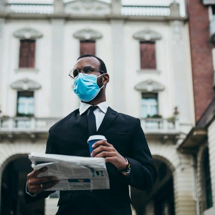 man with face mask holding a cup and newspaper